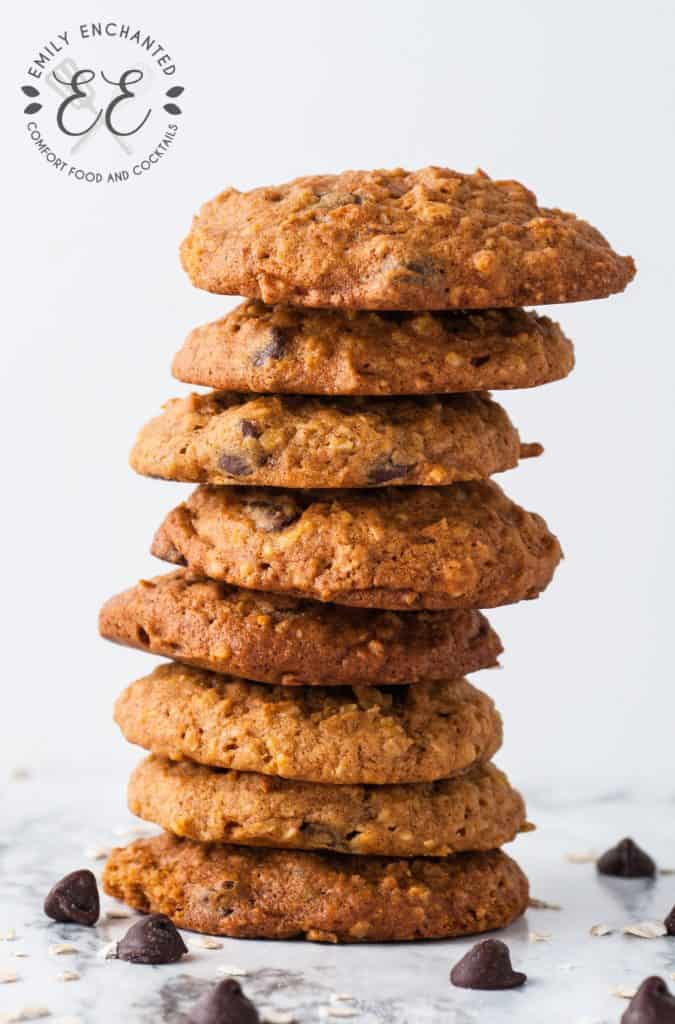 Stack of Oatmeal Pumpkin Chocolate Chip Cookies surrounded by loose chocolate chips on a marble counter top.