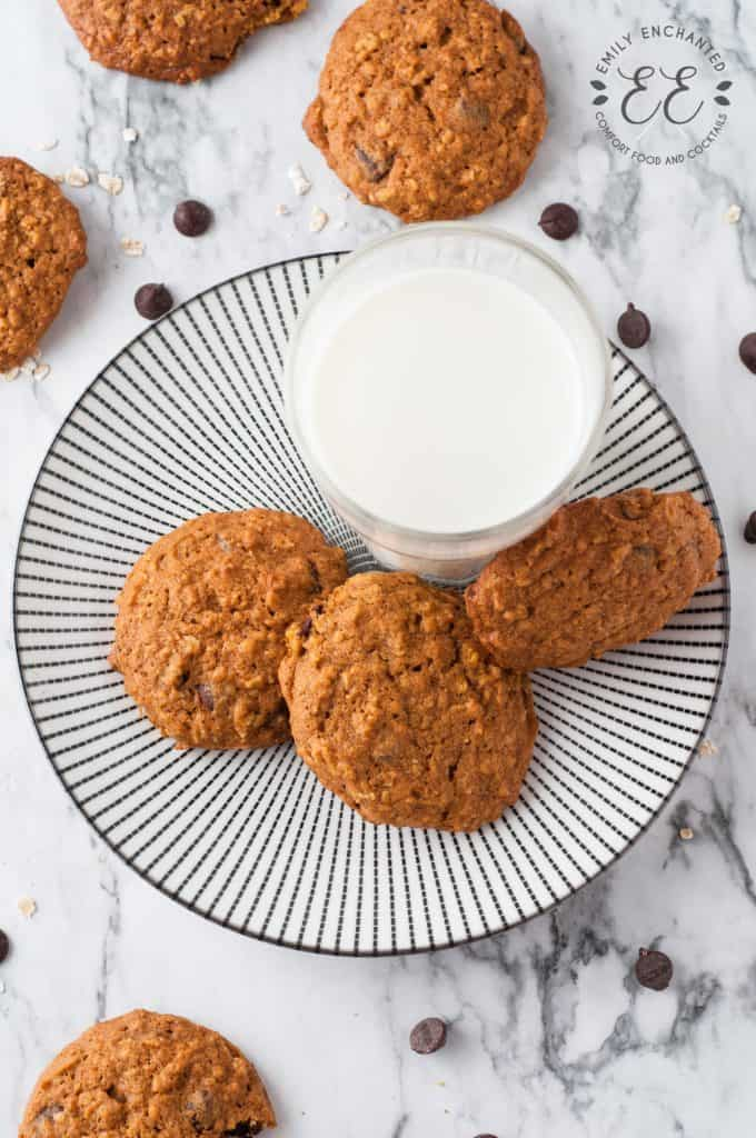 Oatmeal Pumpkin Chocolate Chip Cookies and a glass of milk on a black and white striped plate.