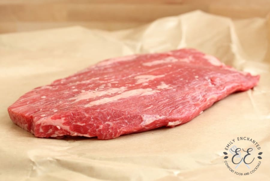Side view of a raw large flank steak on butcher's paper