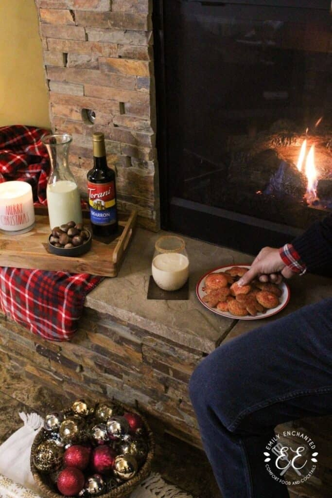 A fireplace mantle with a plate of cookies, holiday drink, and a tray with bowl of chestnuts, Torani syrup, pitcher of eggnog, and a lit Christmas candle