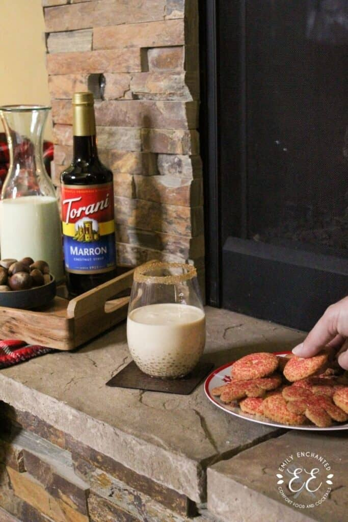 A fireplace mantle with a plate of cookies, holiday drink, and a tray with bowl of chestnuts, Torani syrup, and pitcher of eggnog