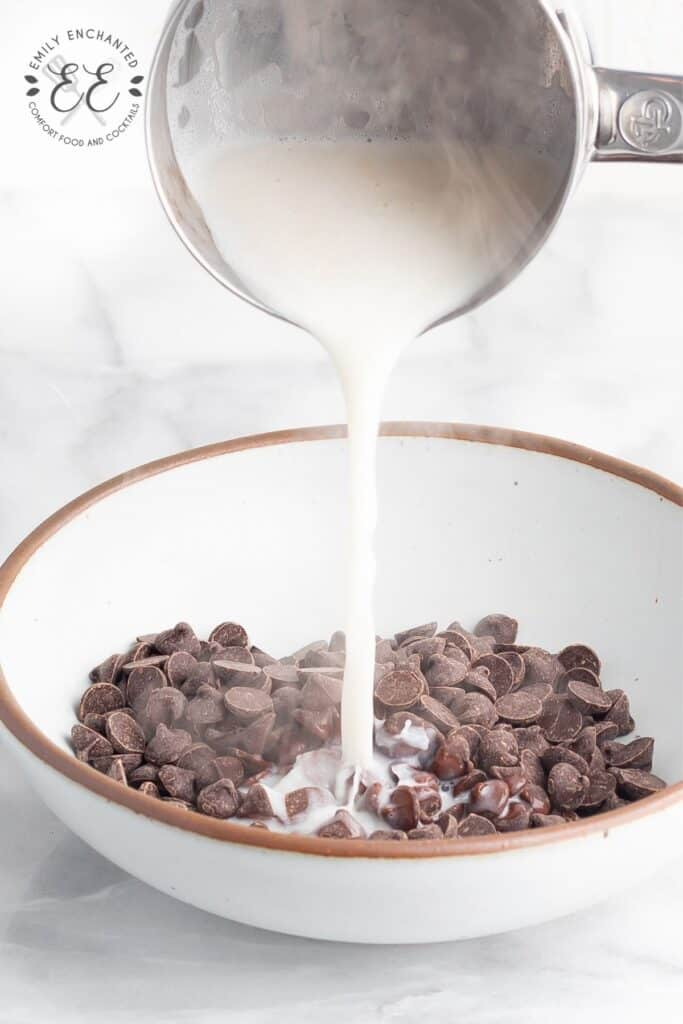Boiling milk being poured over chocolate chips