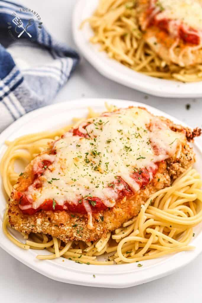 Air Fryer Chicken Parmesan on spaghetti on a white plate with blue checkered towel in background